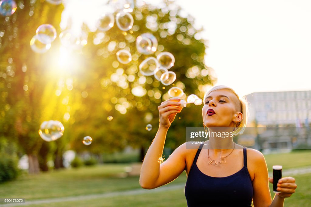 Beautiful blonde hipster blowing bubbles in park