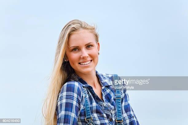Hermosa rubia en camisa azul contra el cielo azul
