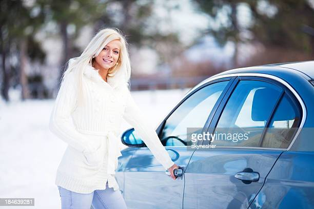 Beautiful blonde lady entering her car.