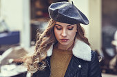 Blonde russian woman in urban background. Beautiful young girl wearing beret, black leather jacket and mini skirt standing in the street. Pretty female with long wavy hair hairstyle and blue eyes.