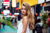Beautiful blonde sexy tourist girl walking in busy city street with long hair flying on the wind. Woman looking at camera outdoors wearing fashionable white t-shirt. New York City lifestyle photo.