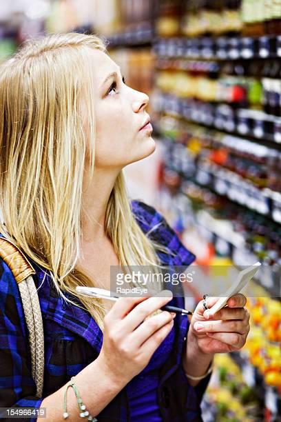 Wunderschöne blonde shopper Schecks shopping Liste von Supermarkt-Regal Inhalt