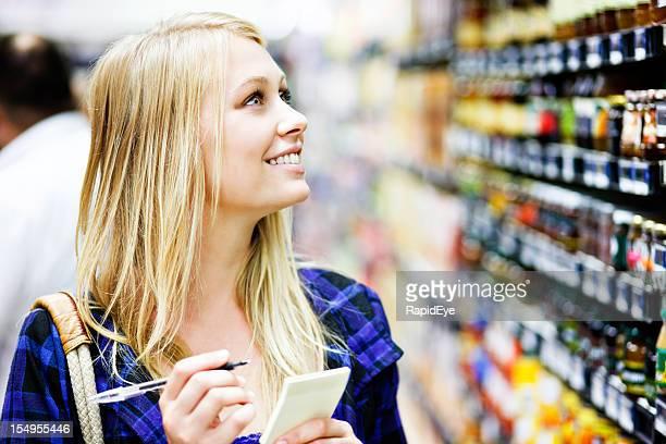 Wunderschöne blonde Einkaufen im Supermarkt, die auf Regal gegen Liste
