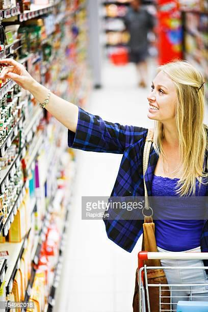 Beautiful blonde shopper reaches up to supermarket shelf