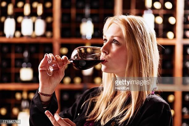 Bela Loira sipping Vinho Tinto no Estabelecimento Vinícola provar center