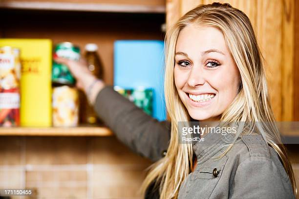 Beautiful blonde smiles as she reaches into grocery cupboard
