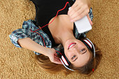 Beautiful blonde smiling woman lying on carpet floor wearing headphones, holding cell phone and listening music portrait. Modern urban life, audio book, radio or education concept