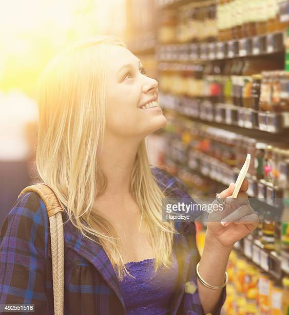 Beautiful blonde supermarket shopper looking up at shelves