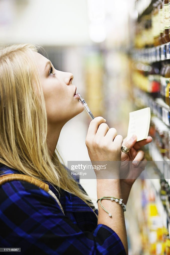 Beautiful blonde supermarket shopper with shopping list makes her selection : Stock Photo