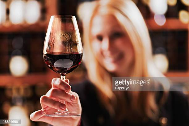 Beautiful blonde tasting red wine in a winery cellar