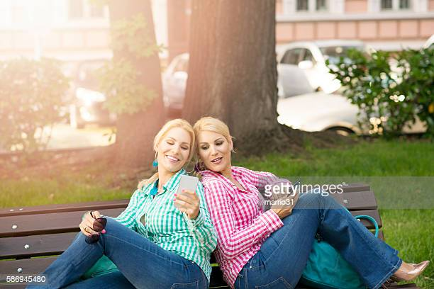Beautiful blonde twins girls with smart phone