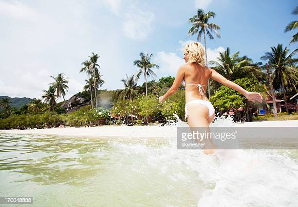 Beautiful blonde woman coming out the water.