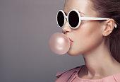 Beautiful blonde woman. Fashion portrait. Blowing bubble gum.