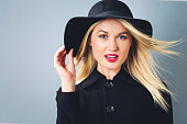 Beautiful young blonde woman in a black coat