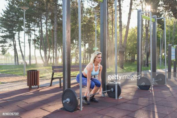 Beautiful blonde woman lifting dumbbell during her fitness workout