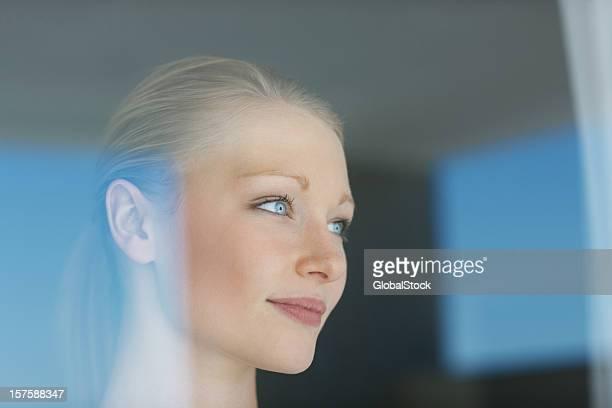 美しいブロンド女性窓の外