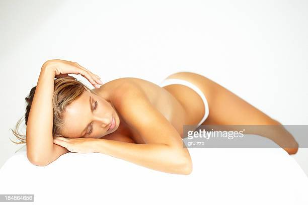 Beautiful, blonde woman lying on bed, waiting for spa treatment