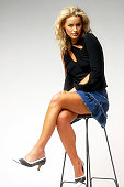 beautiful blonde woman sitting on a stool in a studio.