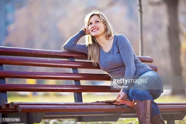 Belle blonde femme assise sur le banc dans le parc.