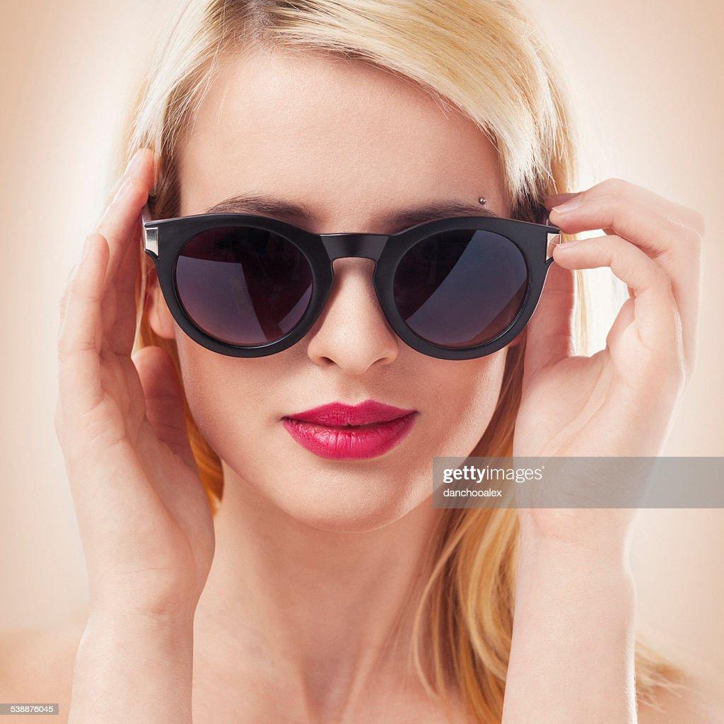 Beautiful blonde woman wearing sun glasses close up shot