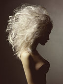 Fashion studio portrait of beautiful blonde woman with volume hairstyle on black background