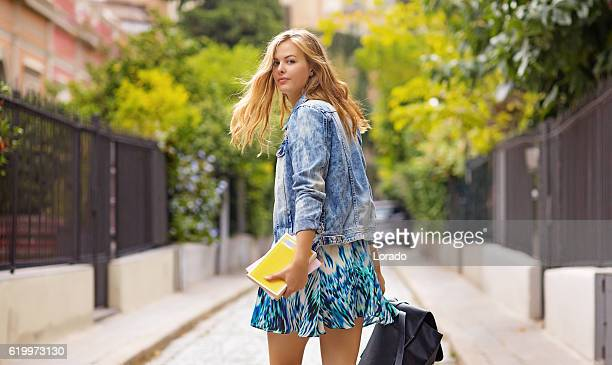 Beautiful blonde young woman student walking in daytime european city