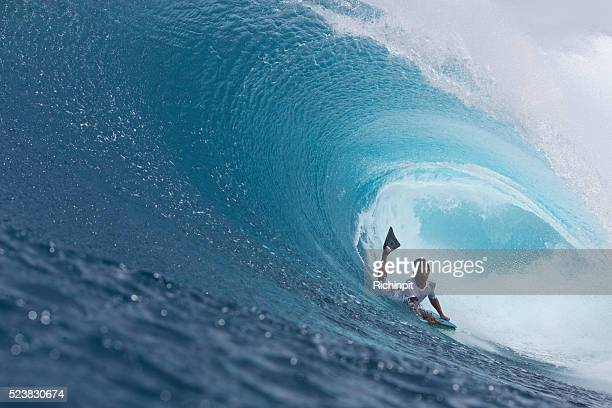 Beautiful blue barreling wave over a bodyboarder
