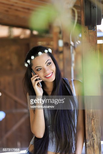 Beautiful boho woman with wreath talking on the phone