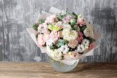 beautiful bouquet of mixed flowers into a vase on wooden table. the work of the florist at a flower shop.