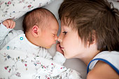 Beautiful boy, hugging with tenderness and care his newborn baby brother at home. Family love happiness concept