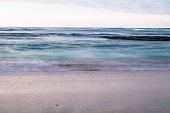 beautiful breaking waves on sandy beach on atlantic ocean in sunset sky, hendaye, basque country, france
