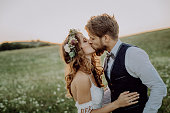 Beautiful young bride and groom kissing outside in green nature at romantic sunset.