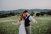 Beautiful young bride and groom with sparklers hugging outside in green nature.