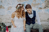 Beautiful young bride and groom outside in front of an old shabby house.
