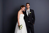 Beautiful bride and groom in studio, smiling