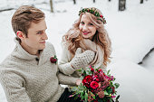 Beautiful bride and groom posing on background of snowy forest. Selective focus on the groom. Copy space
