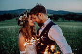 Beautiful young bride and groom on a meadow in the evening, holding sparklers.