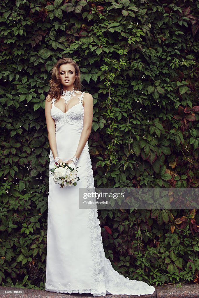 Beautiful bride holding a bouquet of flowers : Stock Photo