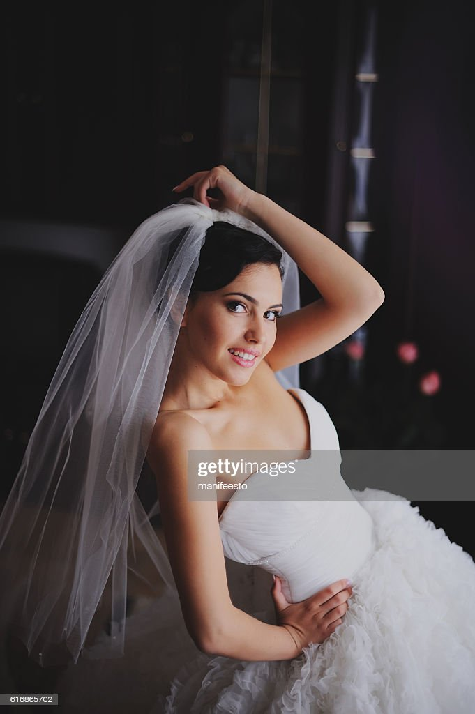 Beautiful bride in wedding dress getting ready : Stock Photo