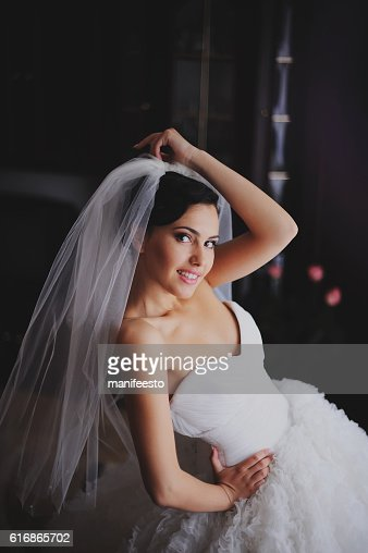 Beautiful bride in wedding dress getting ready : Stock Photo
