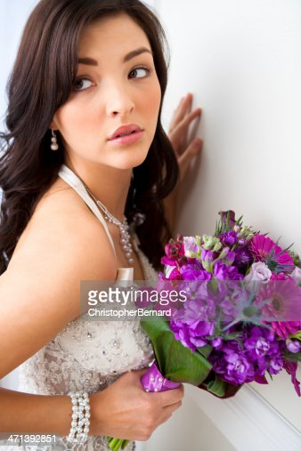 Beautiful Bride leaning on wall