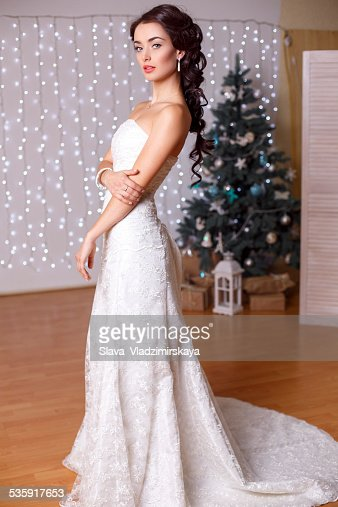 beautiful bride posing in studio with decorated Christmas tree : Stock Photo