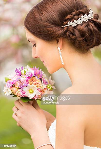 Wunderschöne Braut riechen in ihrem farbenfrohen Hochzeitbouquet