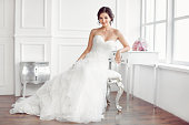 Wedding preparation. Beautiful young bride in white wedding dress indoors. Luxuty model sitting on chair with brides bouquet like at home in studio room with big window. Girl shows wedding fashion in