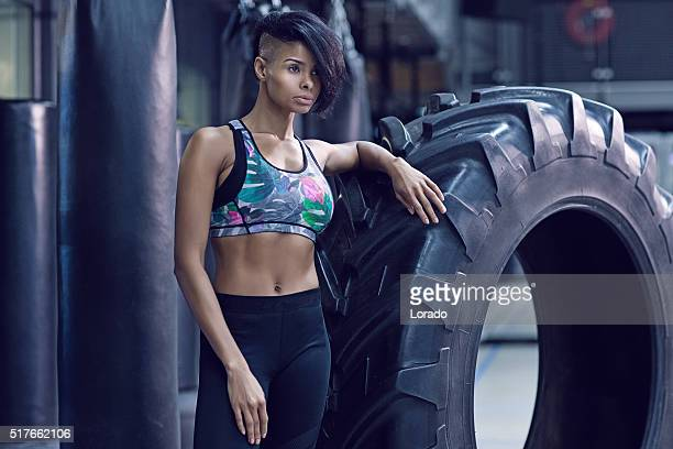 Beautiful brunette athletic woman posing with tyre in a gym