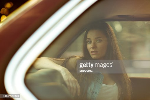 Beautiful brunette behind closed car window, tinted photo : Stock Photo