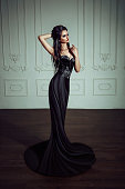 Beautiful brunette girl in a luxurious, black dress. Indian woman in the role of a chess piece. Black queen.