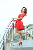 Beautiful brunette in a red dress standing on the stairs. She lifted one leg.