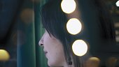 Beautiful brunette is looking out the window, with green background. Closeup, profile. Portrait. Twinkle lights.