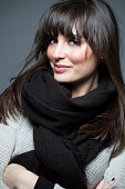 Portrait of beautiful brunette model wearing sweater and scarf.